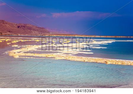 Therapeutic Dead Sea. The evaporated salt is precipitated by picturesque stripes in shallow water. The concept of medical and ecological tourism. Israel