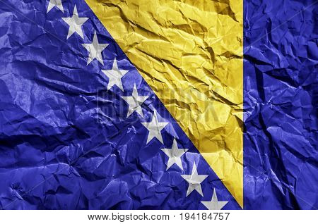 Bosnia and Herzegovina flag painted on crumpled paper background