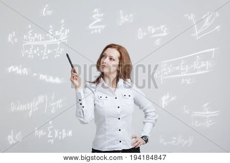 Woman scientist or student with pen working with various high school maths and science formula.