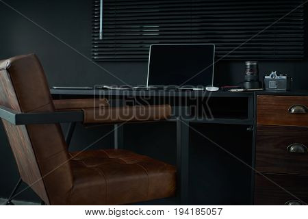 Work space on black table of a photographer or designer with laptop retro camera Stylish home studio concept of hipster . Seleted focus.