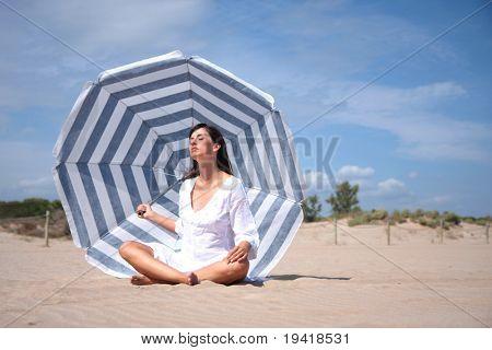 woman having recreatin under blue white striped parasol on the coast