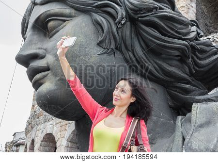 Young woman traveler making selfie photo with details of the Arena in Verona (Italy) and scenic decorations on background. Shallow DOF.