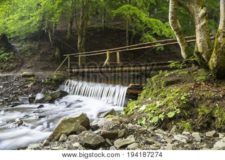 Fast mountain river flowing among stones and boulders in green forest. Handmade wooden bridge over the river . Spring in Carpathians Ukraine