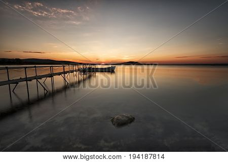 A Traditional Wooden Fishing Boat In The Sea. Boat In The End Of The Old Wooden Pier. Fishing Boat T