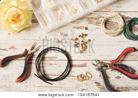 Workspace with tools for making jewelry - pliers leather earrings and bracelets necklace. Kraft tools. Bright rustic wooden desk table