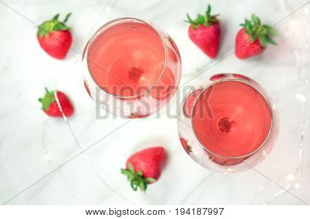 A high-key overhead photo of two glasses of rose wine with strawberries and fairy lights, on a white marble texture with a place for text. Selective focus