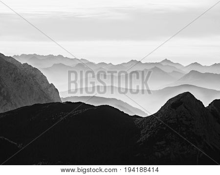 Sharp Mountain Silhouettes. Distant Mountain Range And Heavy Clouds Of Colorful Mist