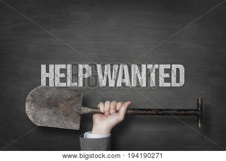 Cropped hand of businessman holding shovel under help wanted text on blackboard