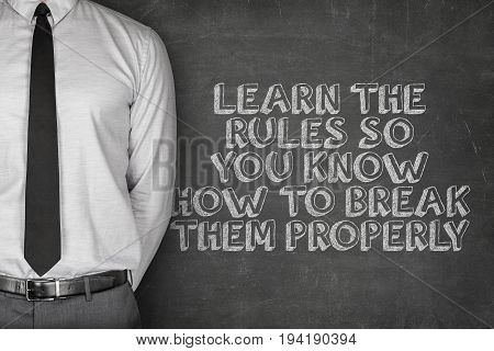 Midsection of businessman standing by learn the rules so you know how to break them properly text on blackboard
