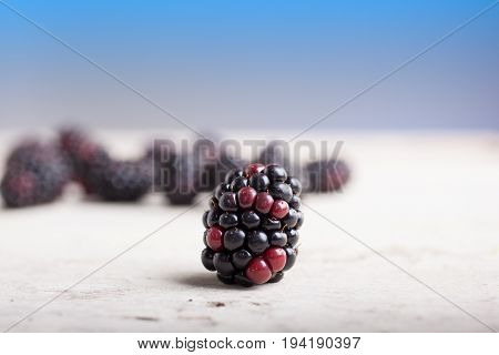 Close up of delicious blackberry on white wooden table