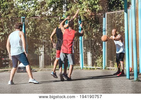Multiethnic Group Of Basketball Players Playing Basketball On Court