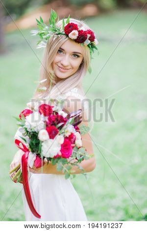 Dainty Young Woman Looks Over Her Shoulder While Posing With Red Bouquet