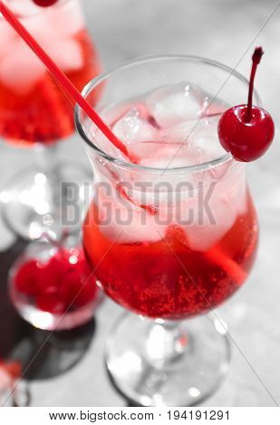 Tequila cocktail with ice cubes and cherry on table