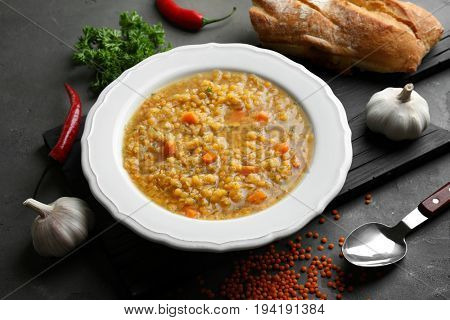 Plate with tasty lentil soup and ingredients on dark table