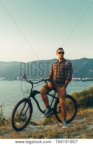 Handsome Young Man Standing With Bike On Coast And Enjoying View of Nature Sunset Vacation Traveling Relaxation Resting Concept