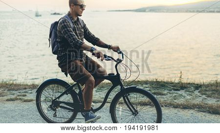 Handsome Young Hipster Man Is Cycling Along The Shore Against The Backdrop Of The Sunset Vacation Holiday Activity Concept