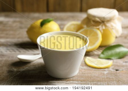 Bowl with delicious lemon curd on wooden table
