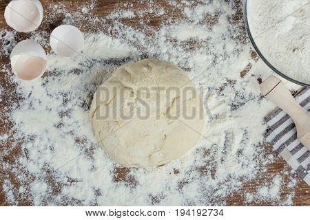 Top View Of Fresh Unbaked Dough In Flour On Wooden Table Top