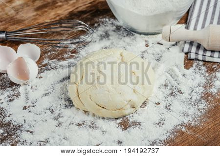 Close-up View Of Fresh Unbaked Dough In Flour On Wooden Table Top
