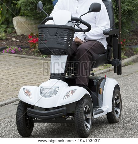 white electric motorised wheelchair on the street