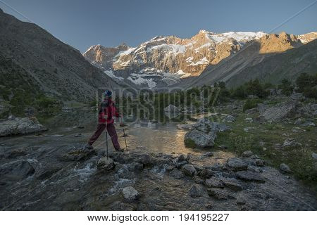 Woman with sticks crossing stream. High mountains with snow in background. Woman is looking at beautiful mountains.
