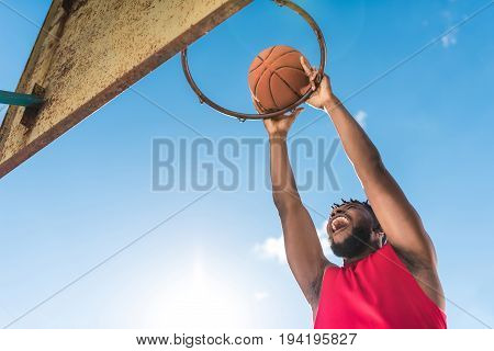 Low Angle View Of African American Basketball Player Throwing Ball Into Basket