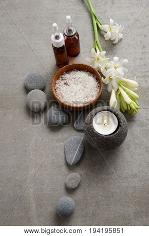 Spa setting Hyacinth with and stone, salt in bowl,oil, candle on gray background
