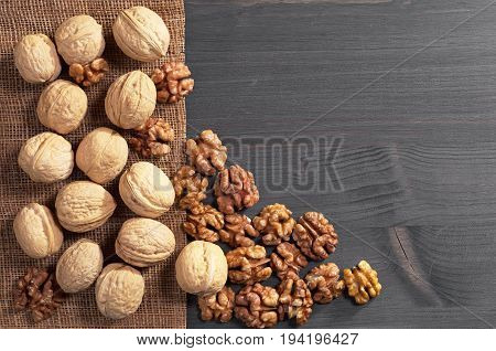 Walnut kernels and whole on dark wooden table top view. Space for text