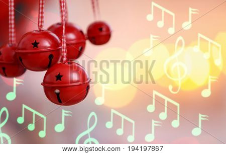 Jingle bells and notes on blurred lights background. Concept of Christmas music and songs