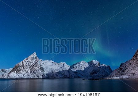 Delicate soft northern lights over snowy mountains in moonlight and starry sky at Lofoten Norway
