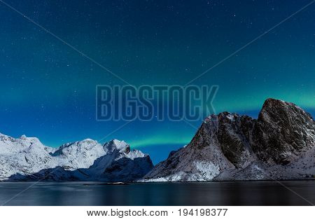 Starry sky with northern lights ofer steep snow covered rocky mountains in northern Norway at winter