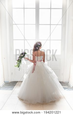 Bride with a bouquet of flowers in full growth against the backdrop of a glowing door. New life, light