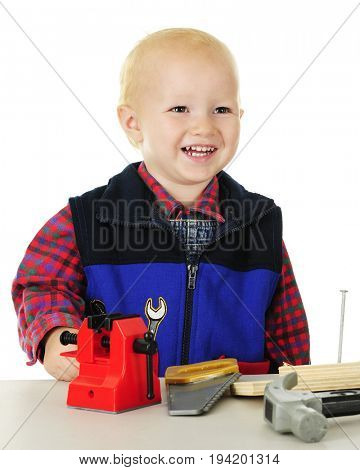 Closeup image of a happy toddler standing at his tool table with a toy vice, saw, and hammer.  On a white background.