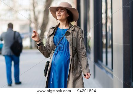 Elegant style of a pregnant woman in a modern city. Fashion trends for pregnant women