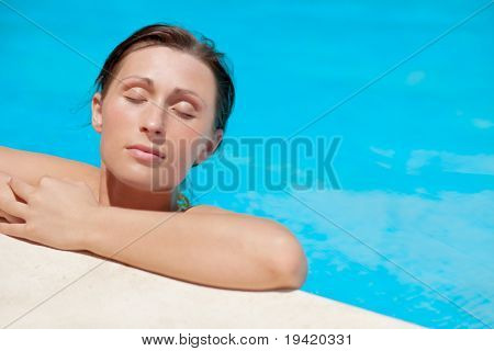 Clean tan summer tanning woman lying on the pool