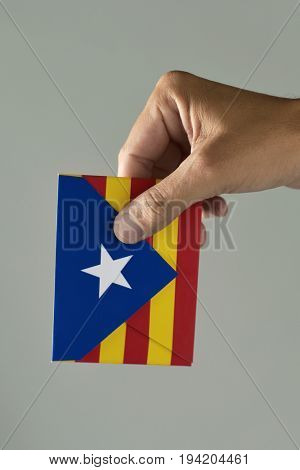 closeup of a young man with an envelope patterned with the Estelada, the Catalan pro-independence flag, depicting the Catalan independence referendum poster