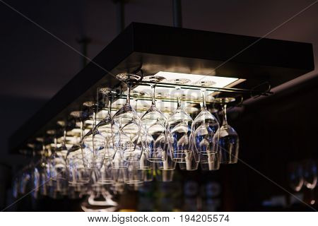 Empty wine glasses hanging upsidedown in bar interior. Classic wineglasses hanger on restaurant or pub background