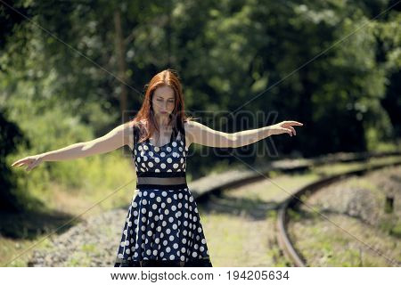 Young woman walking on railway track balancing with her arms extended. Woman in spotted dress and red hair.