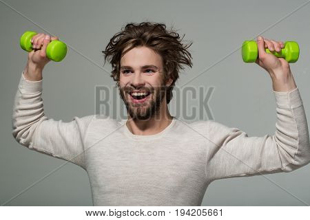 happy man with barbell or dumbbell workout has disheveled and uncombed long hair and beard on face in white underwear on grey background morning exercise and wake up barbershop sport