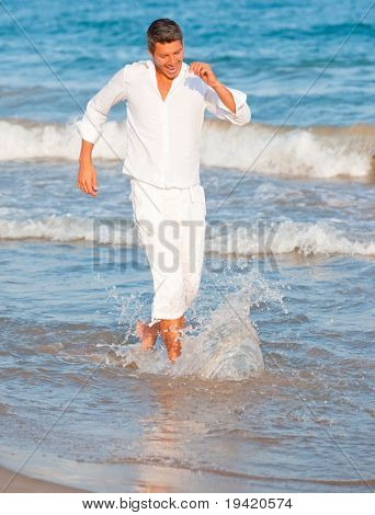 Playful healthy smiling funny man walking down seaside playing with ocean water being dynamic with motion