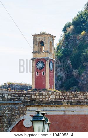 Old Byzantine clock tower on green mountains background. Greece, Corfu