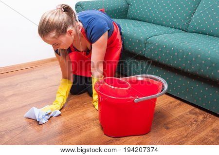 Young Housekeeping Lady Wiping The Wooden Floor