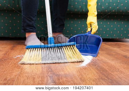 Woman Sweeping Floor With Broom And Dustpan