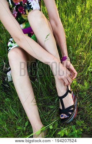 Woman sitting in the grass and fastening the high heel sandals.