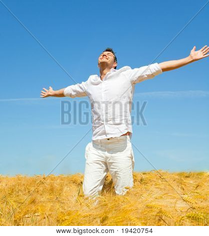 Carefree man standing in golden wheat field being happy enjoying freetime