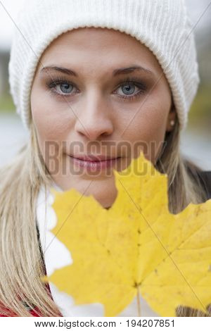A beautiful, young woman holds a leaf