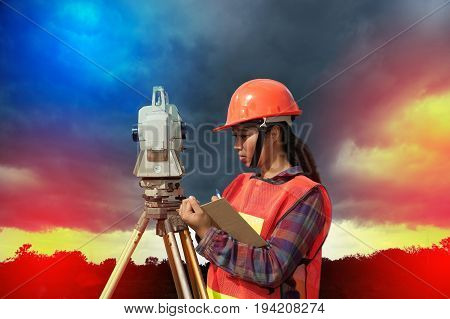 Female Surveyor or Engineer making measure by Theodolite in a field and colorful sky background.