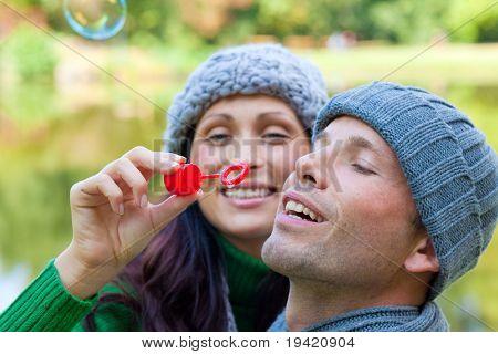 Funny playful autumn fall couple making soapbubbles