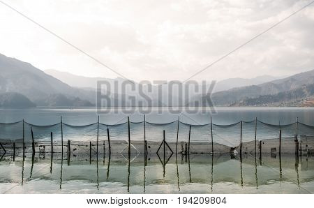 Trap in the form of a fishing net tense through the mountain lake Pheva in the Himalayas fencing off part of lake.