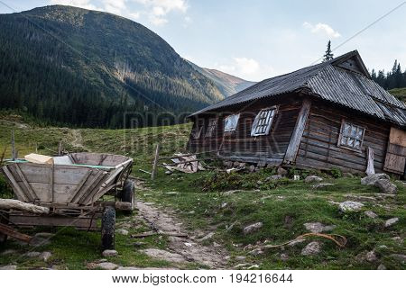 Wooden shepherds' house in the Ukrainian Carpathians with wooden cart nearby.